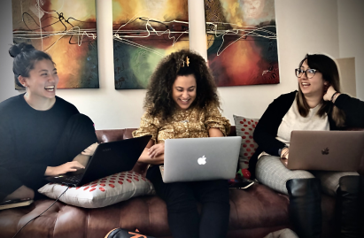 Image of three people working on laptops together and smiling. This image depicts how working with a psychiatrist in New York City or a nurse practitioner can help your mental health.   11211   10001   10002