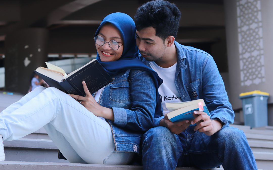 """Image of two people wearing denim outfits reading outdoors together. This image represents the happiness you can find after seeking depression treatment in New York City for a depressive episode. Those searching """"how to deal with depression"""" can benefit from meeting with a depression therapist in New York City. 11211 