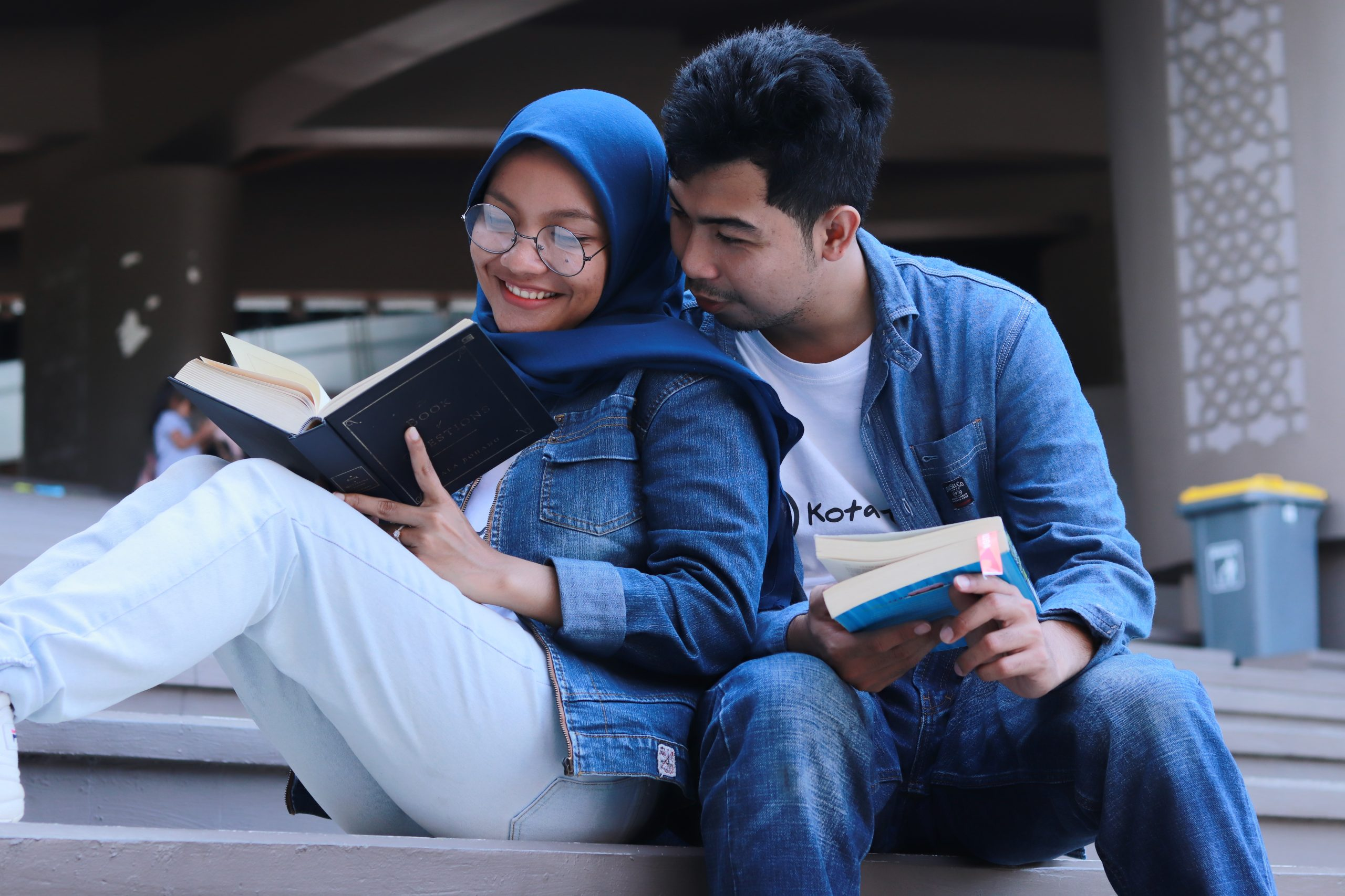 """Image of two people wearing denim outfits reading outdoors together. This image represents the happiness you can find after seeking depression treatment in New York City for a depressive episode. Those searching """"how to deal with depression"""" can benefit from meeting with a depression therapist in New York City. 11211   10010   10003"""