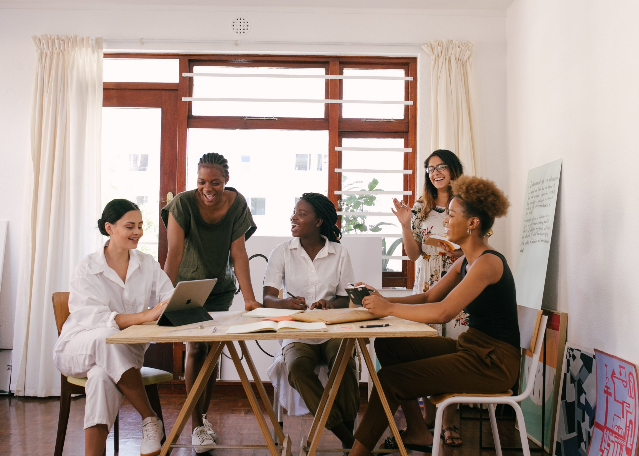 Image of a table of women having a meeting around a table. This image illustrates how those who have undergone bipolar disorder treatment in New York City can lead bustling professional lives. | 11211 | 10018 | 11103