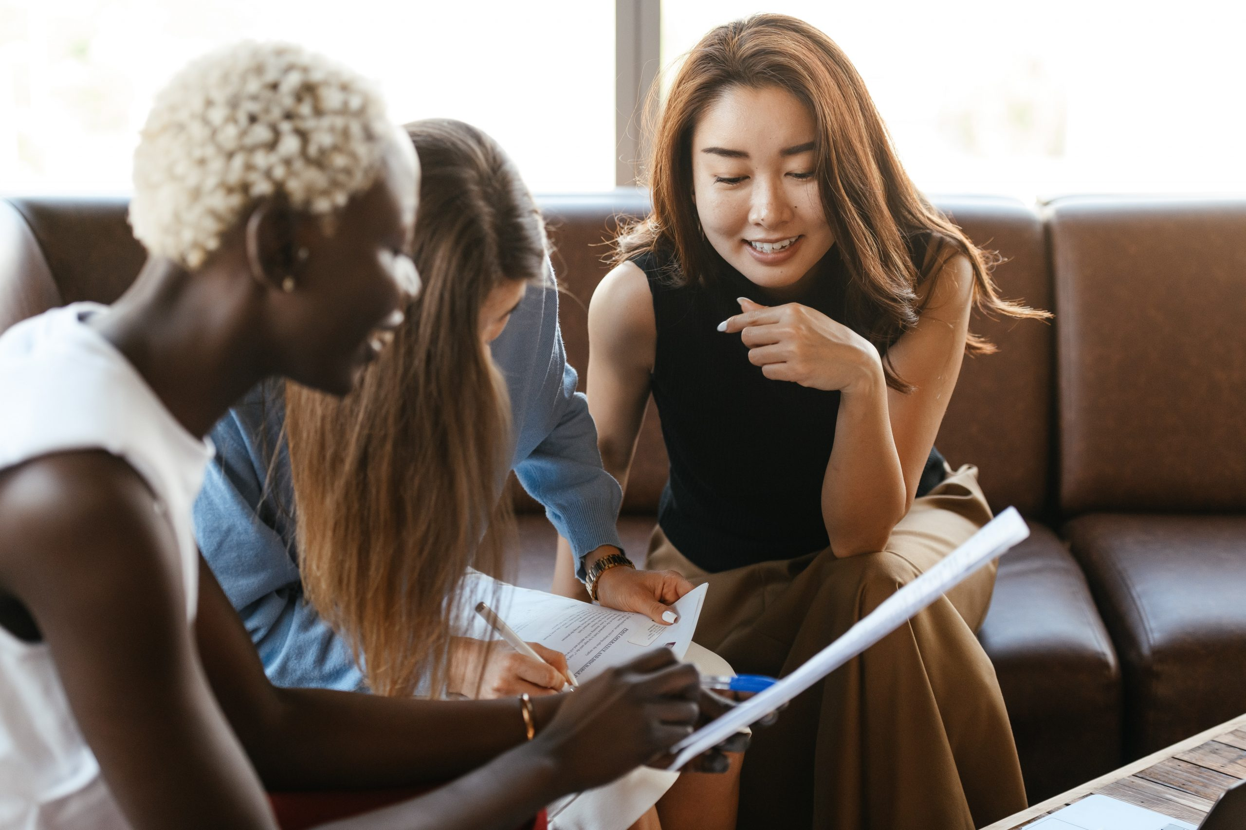 Image of a table of women having a meeting around a table. This image could depict how anxiety treatment in New York City with an anxiety therapist can help you connect with others again. | 11211 | 10018 | 11103