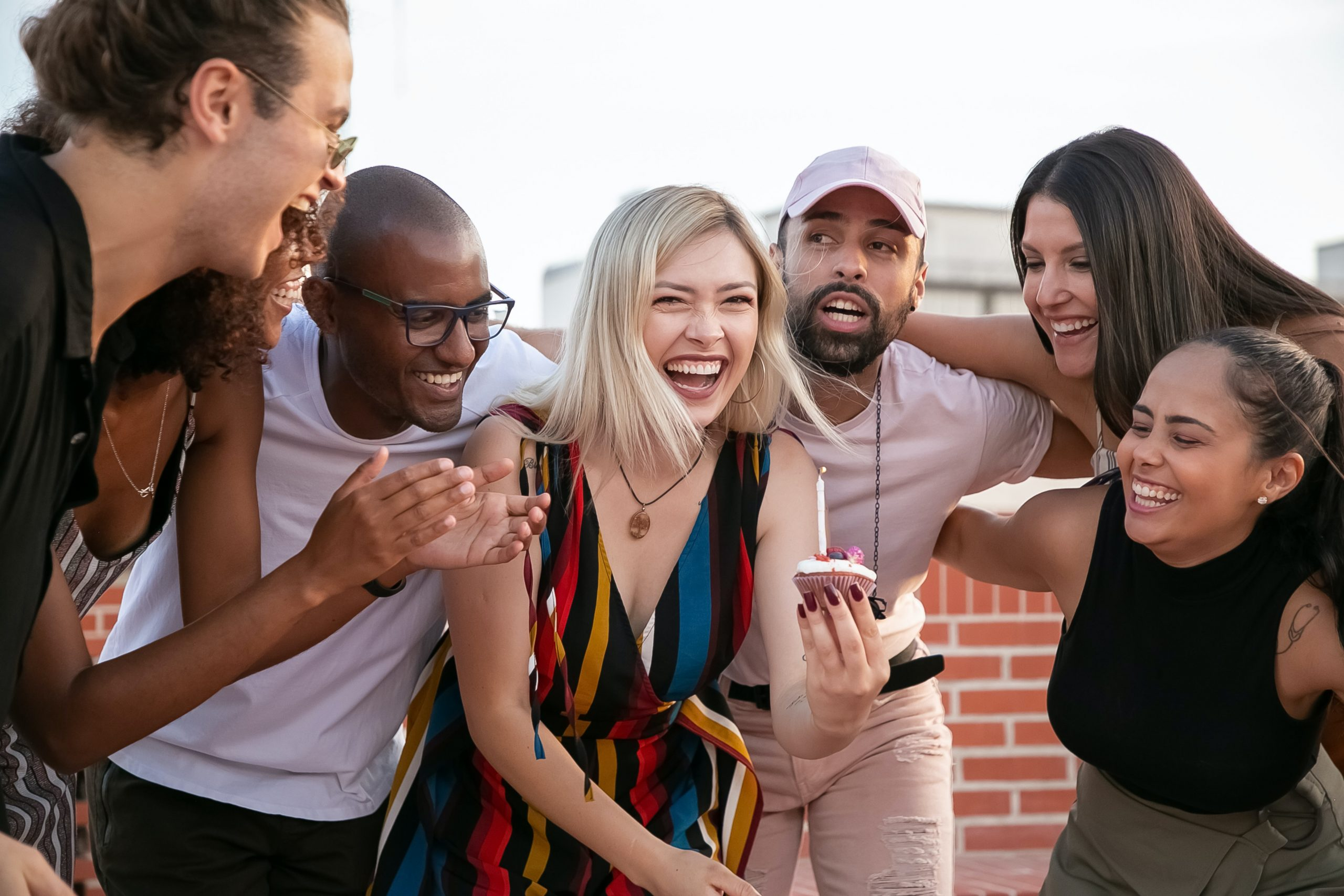 Image of a group of people smiling and celebrating together. This image illustrates how meeting with a depression therapist for a depressive episode can help. Depression treatment in New York City can help you battle depression symptoms. | 11211 | 10002 | 10010