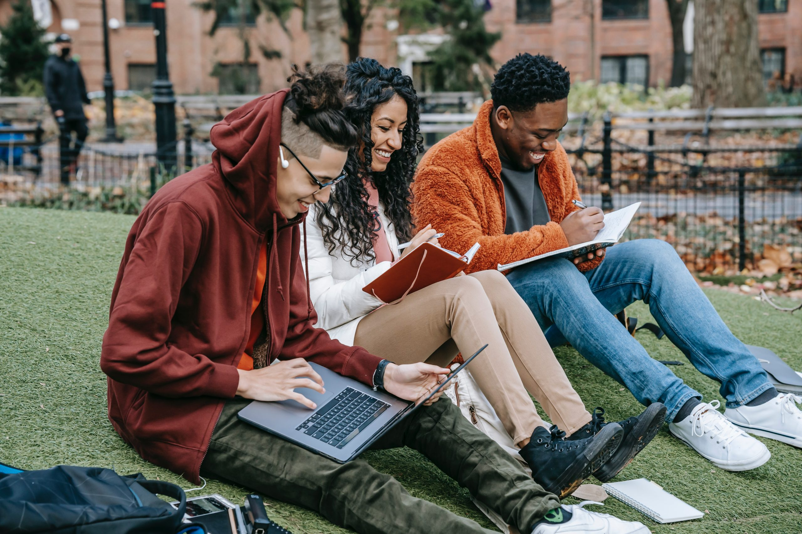 Image of three students sitting together in a park and working in journals and laptops. This image represents how young adults can benefit from working with an ADHD therapist in ADHD treatment in New York City. 10003 | 10002 | 10001