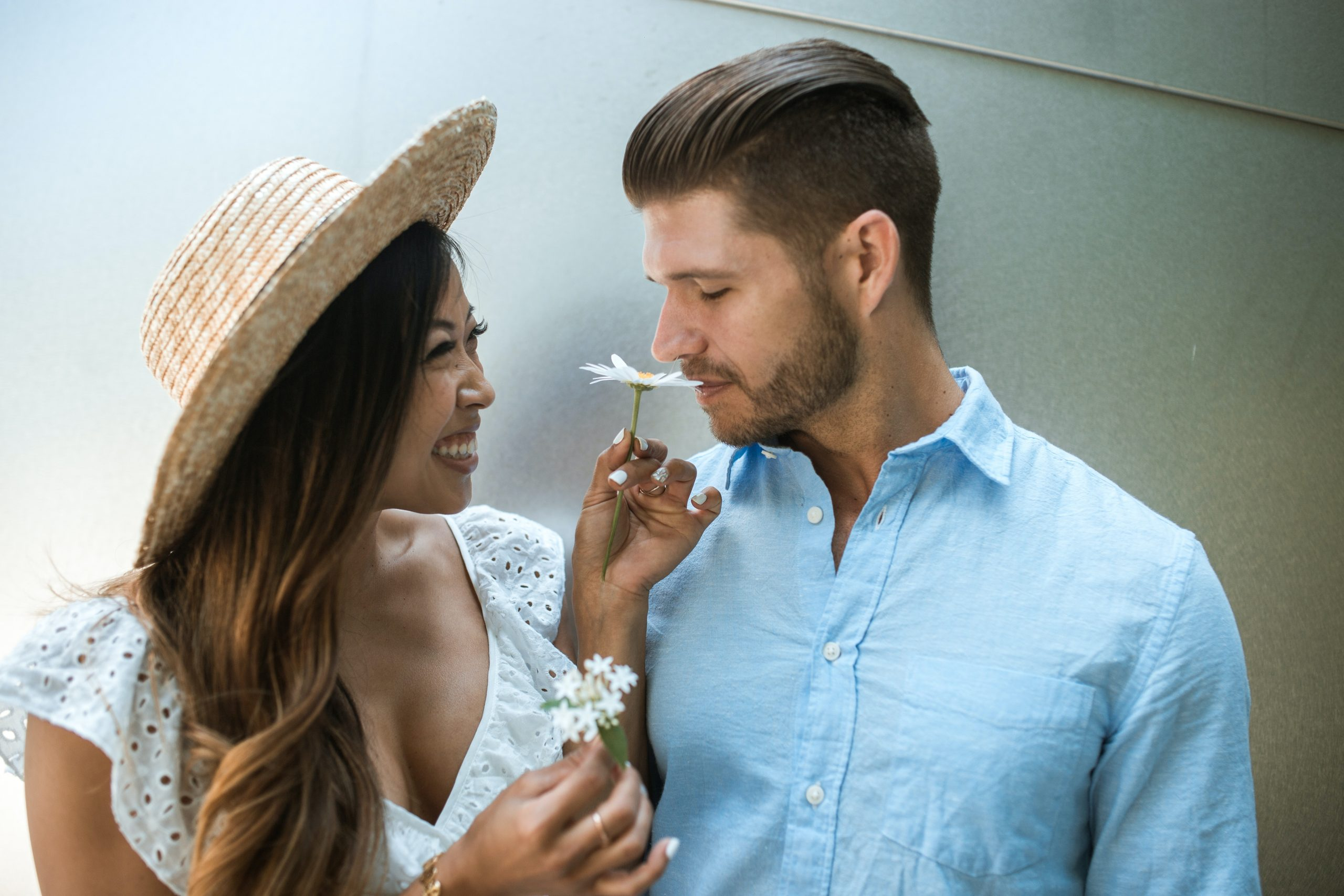 Image of a man and woman standing together and sniffing daisies. This image depicts that someone can have a happy relationship after doing psychosis treatment in New York City. 10005   10003