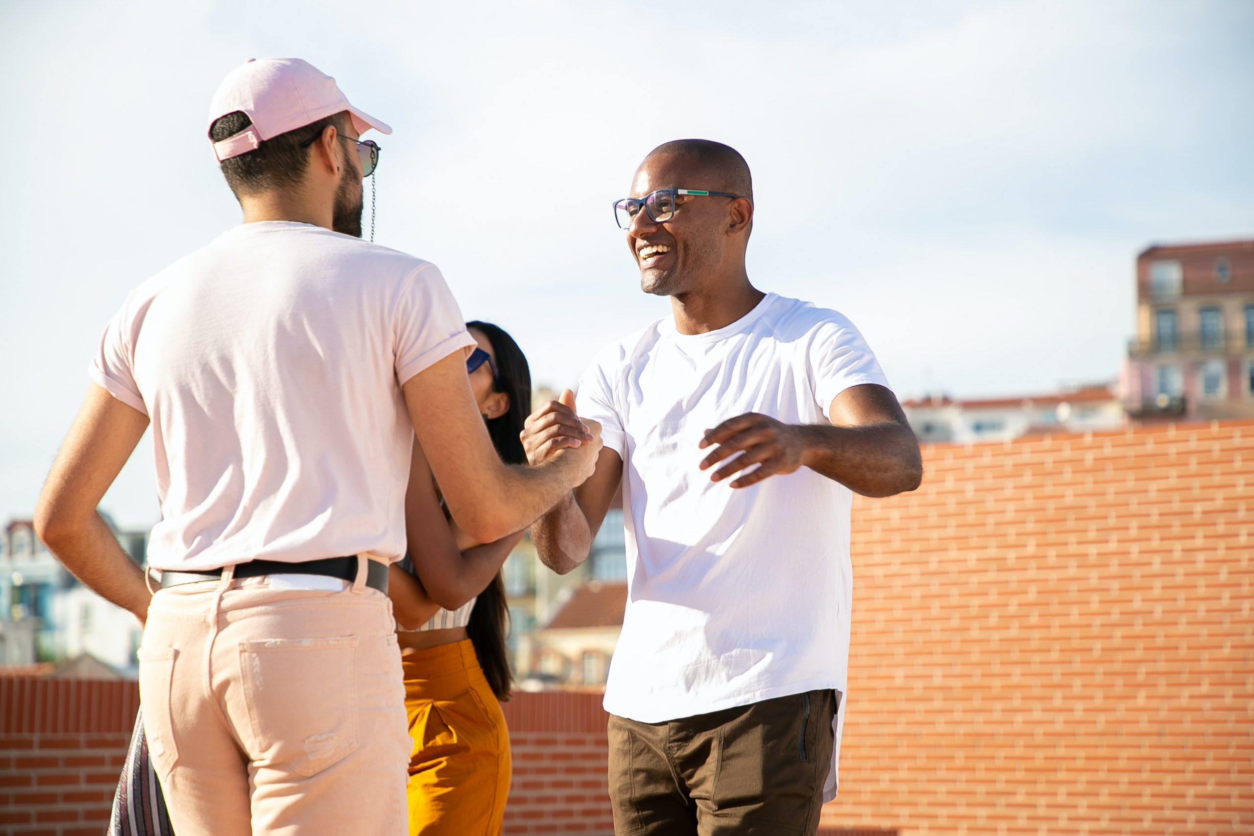"""Image of two people sharing a handshake on a rooftop. This image illustrates how someone searching """"psychosis symptoms"""" could look after psychosis treatment in New York City. 10010 