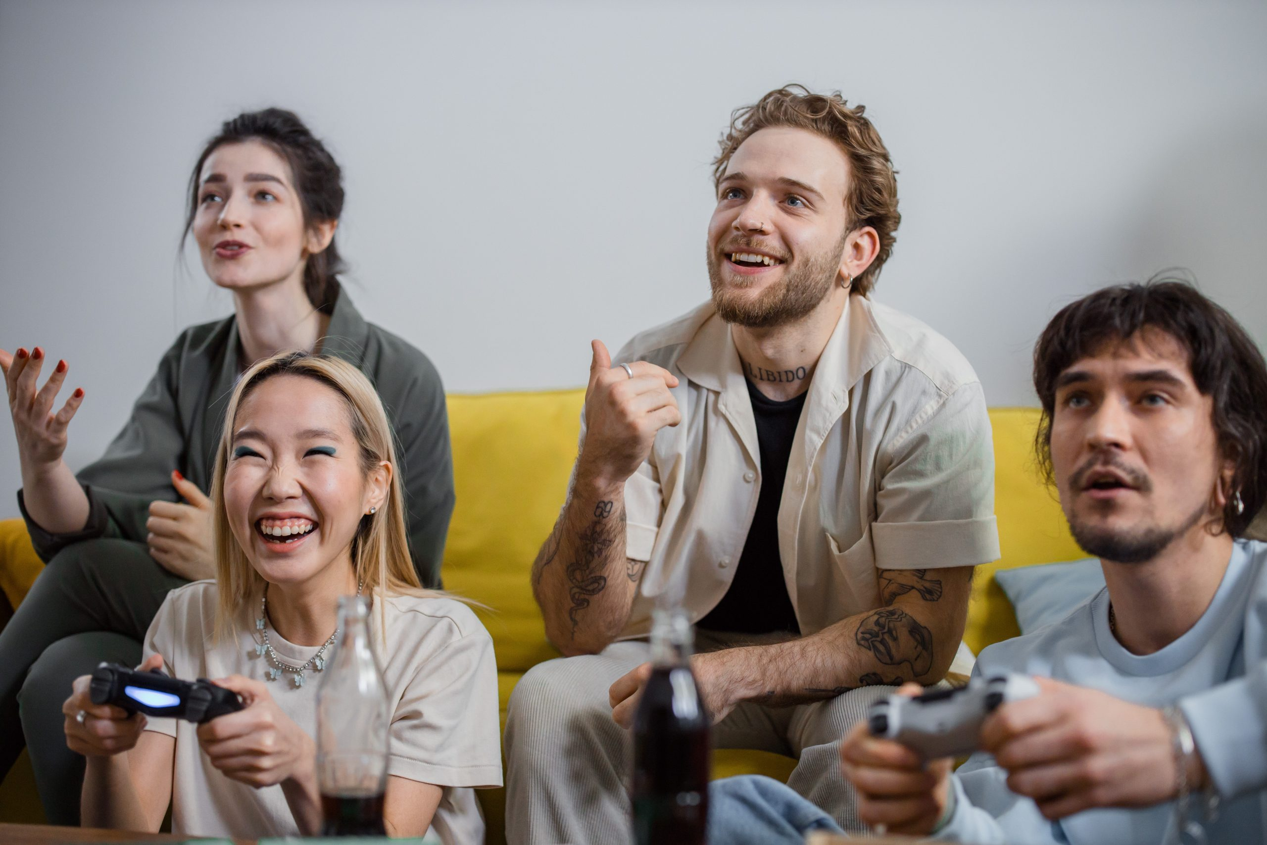 Image of friends hanging out, sharing snacks and playing/watching video games. This image represents how individuals can benefit from working with an autism therapist for ASD treatment in New York City. 10003   10002   10001
