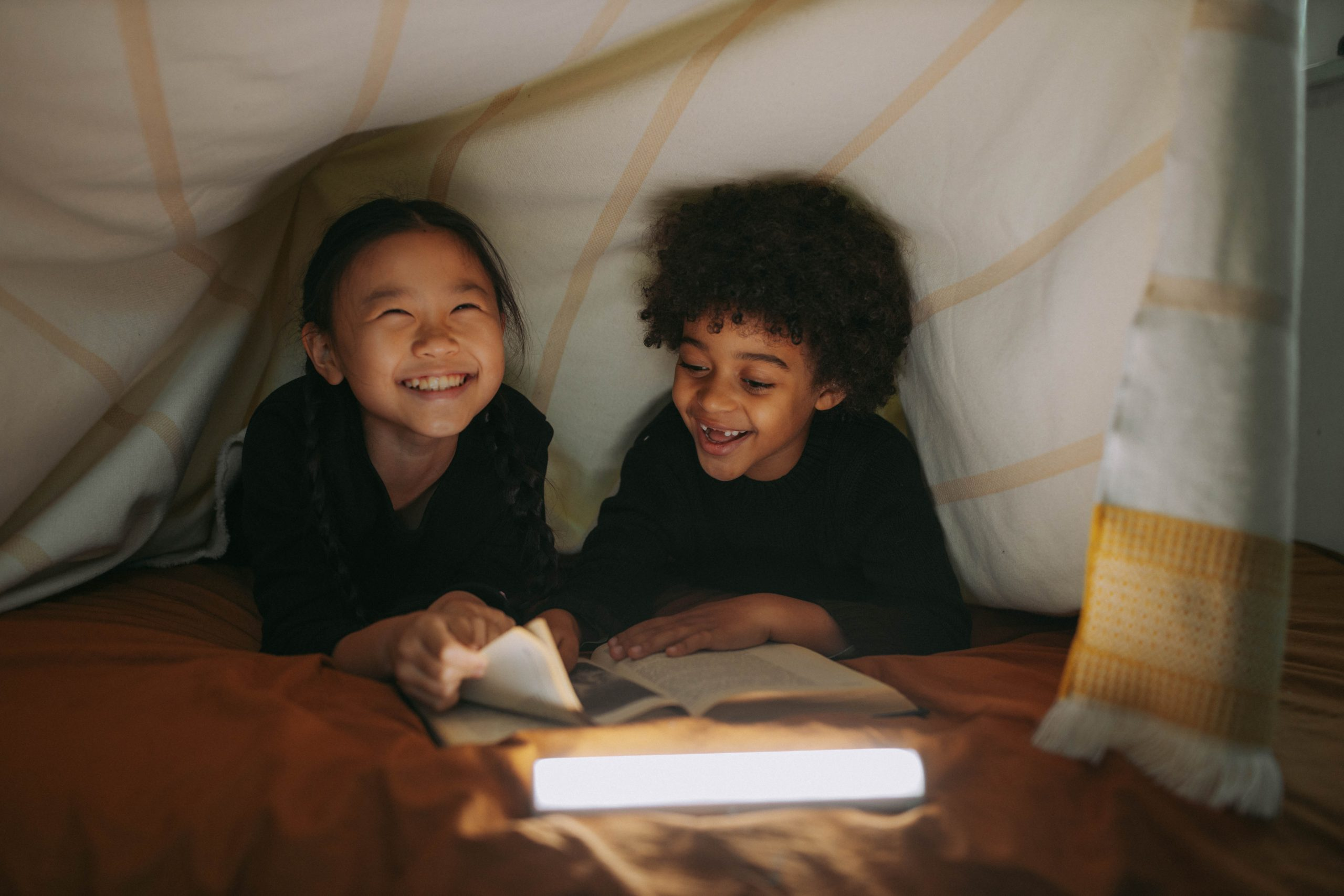 Two kids under a blanket fort reading a book. Having ASD can make socializing more difficult. This photo could represent the social challenges that ASD treatment in NYC can help overcome. Talk to an autism therapist today to get started with autism spectrum disorder treatment in New York. 10005   10003