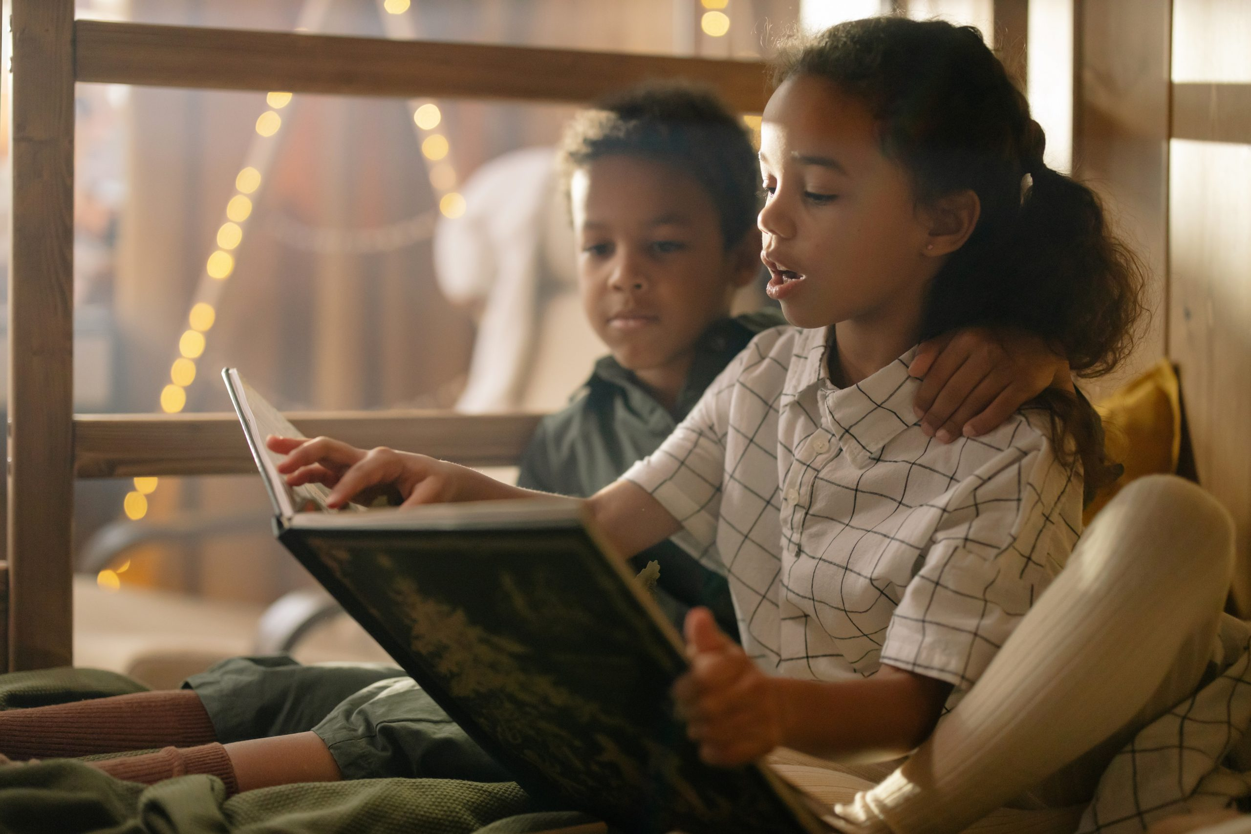 Image of two children reading together on the floor. This image depicts how children may behave while waiting to meet with a trauma therapist for trauma therapy in New York City. 10001 | 10002City.