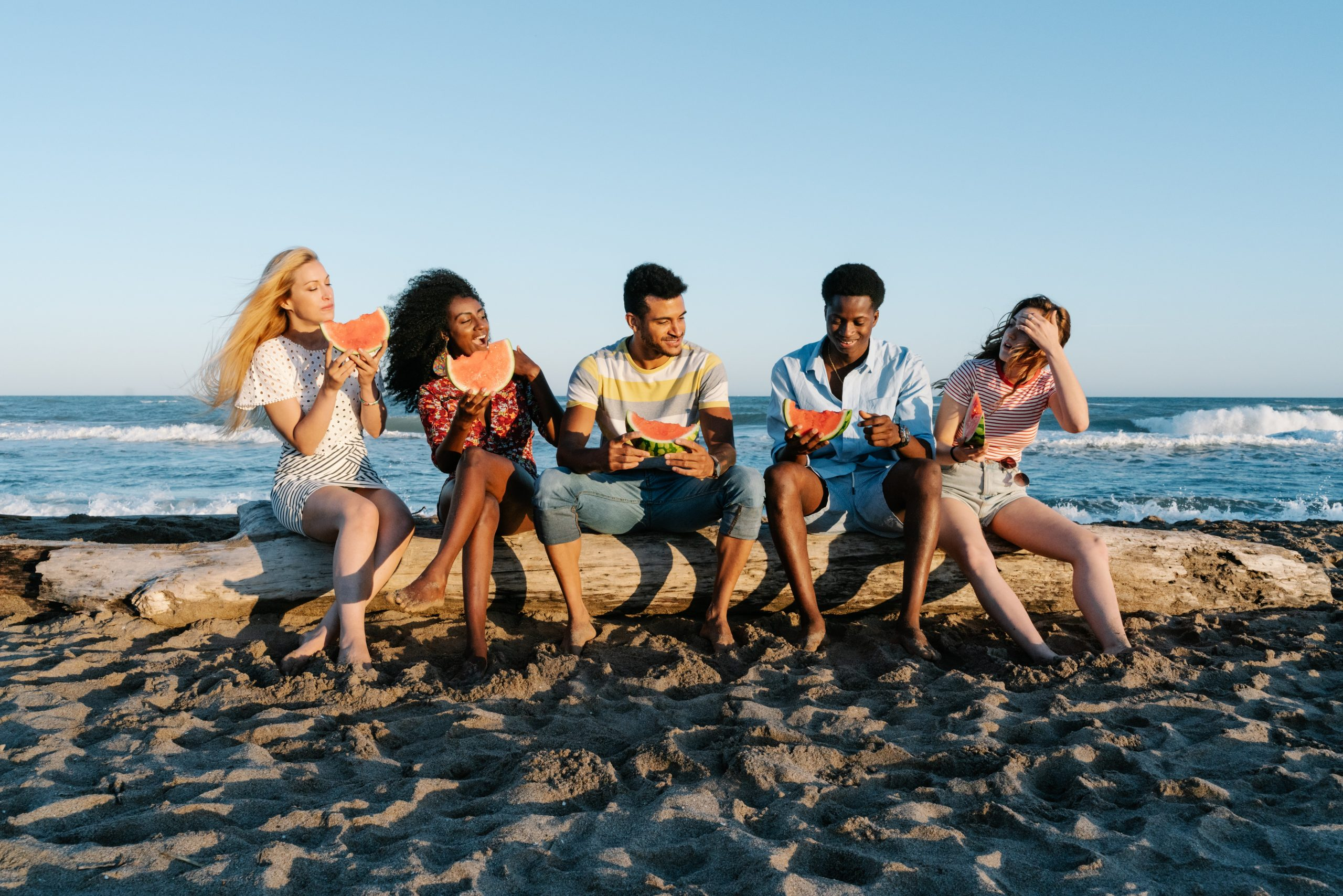 Image of a group of people sitting on a log on a beach eating watermelon. This image depicts how people may interact after sessions with a trauma therapist for PTSD treatment in New York City. 10010 | 10011