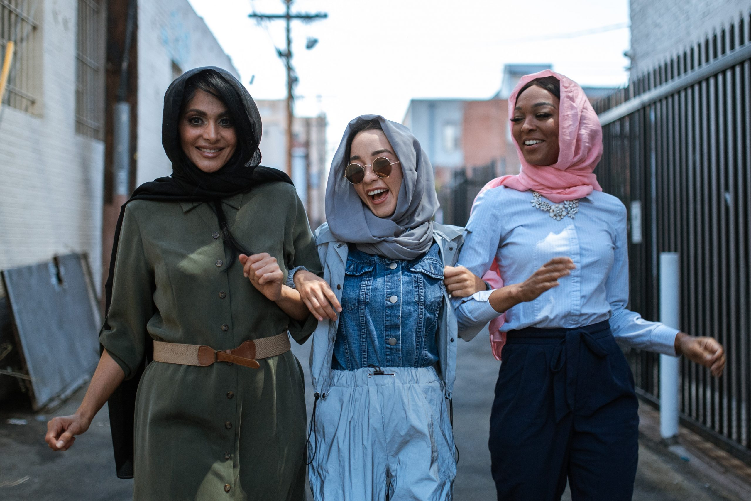Image of three people walking together down an alley. This image demonstrates the friendships folks can develop after PTSD treatment in New York City with a trauma therapist. | 10005 | 10003